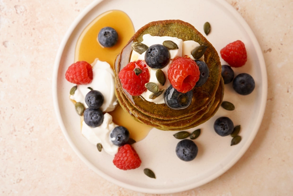 a stack of matcha pancakes from above topped with vegan yogurt, blueberries, raspberries and maple syrup