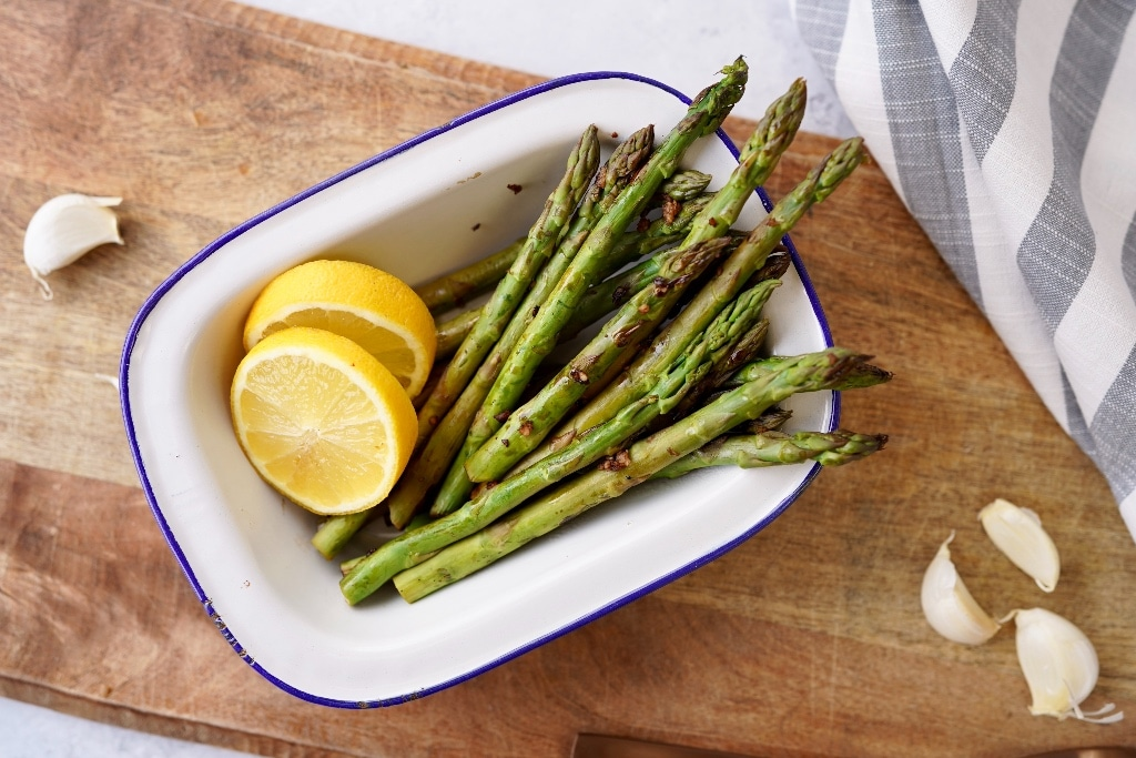 the cooked skillet asparagus in a serving dish with lemon slices and garlic cloves around it