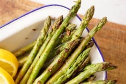 the cooked skillet asparagus heads with crispy garlic pieces and lemon wedges