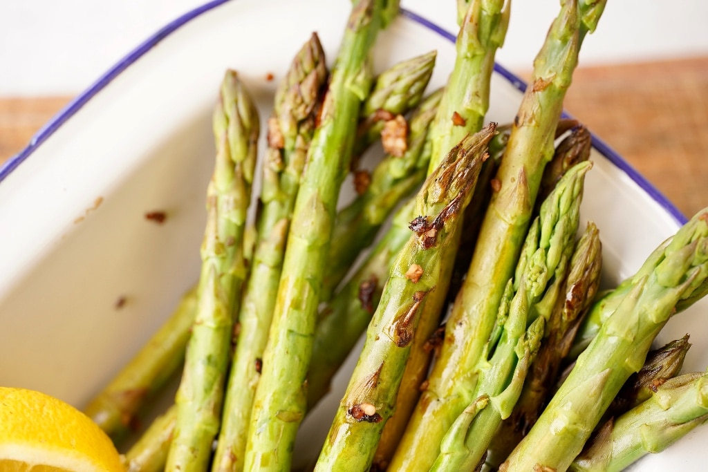 the skillet asparagus spears in a dish, showing the crispy cooked garlic and some lemon wedges