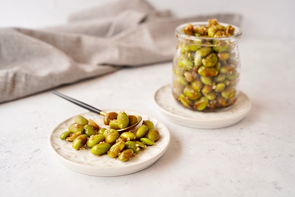 edamame snack recipe beans on a small dish next to a jar of beans