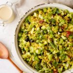 the mediterranean quinoa salad with a serving spoon next to it and a pot of dressing