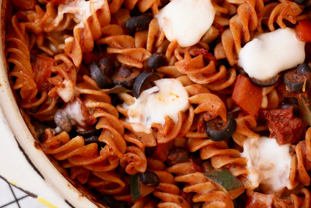 a close up of the vegan pasta bake with partially melted feta on top
