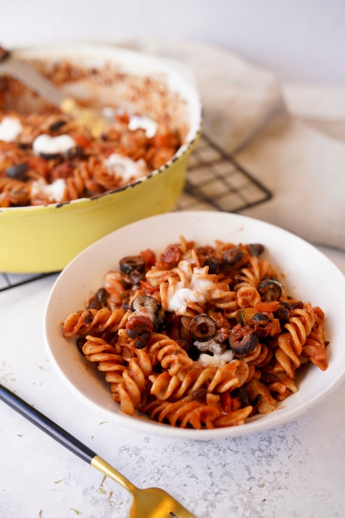 vegan pasta bake in a dish with a portion in front of it in a bowl