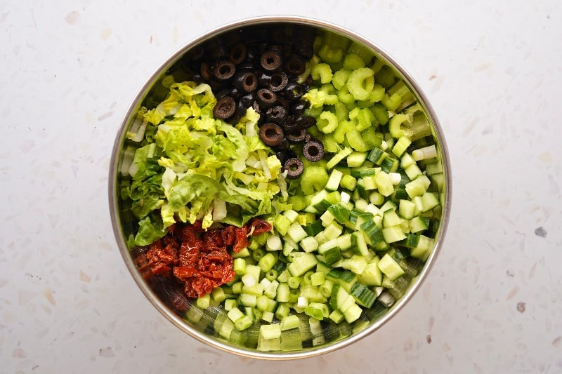 ingredients for the mediterranean quinoa salad in a bowl