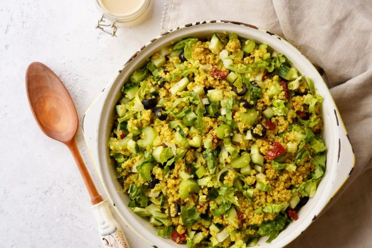 the mediterranean quinoa salad with a serving spoon next to it