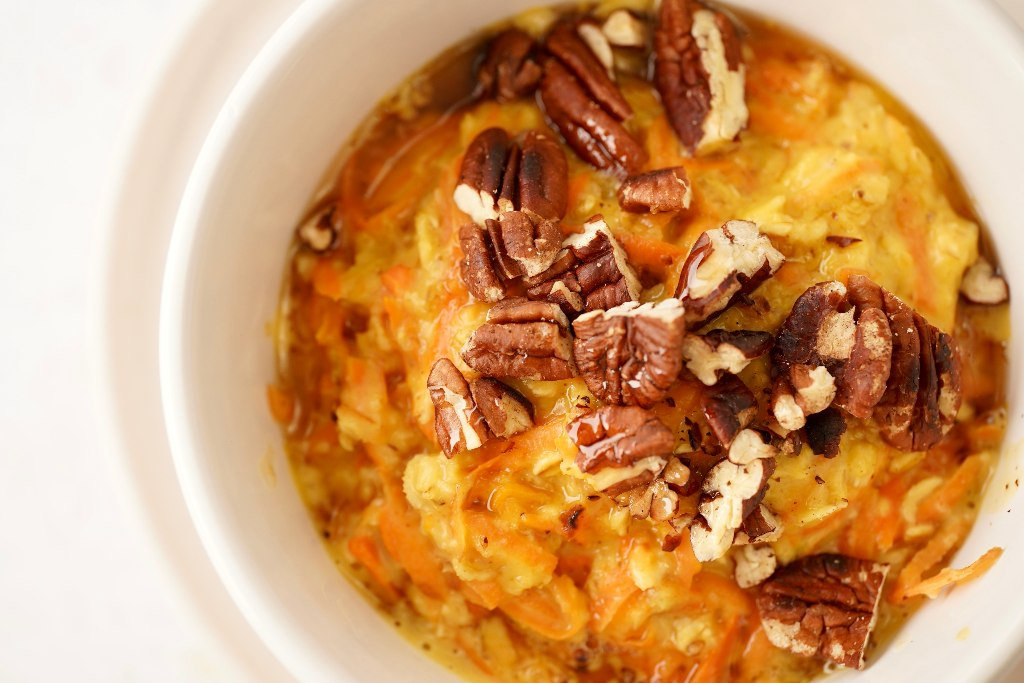 the vegan carrot cake oatmeal topped with chopped pecan nuts and maple syrup