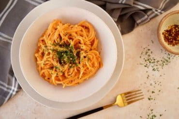 the roasted red pepper pasta sauce on spaghetti pasta topped with dried parsley in a bowl next to a fork
