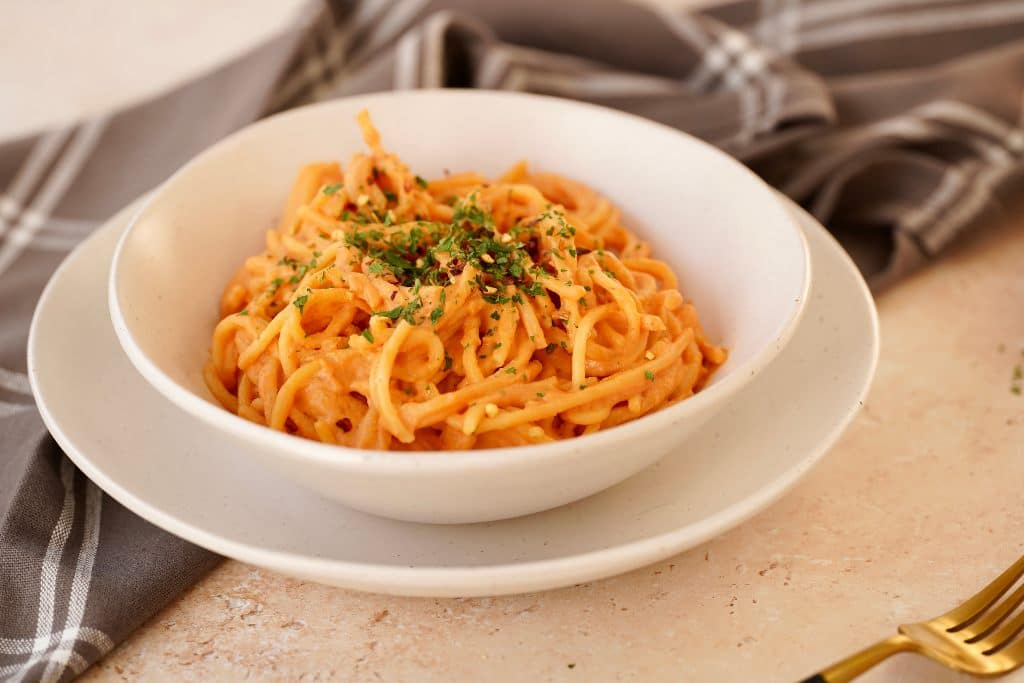 the roasted red pepper pasta sauce on spaghetti pasta topped with dried parsley in a bowl