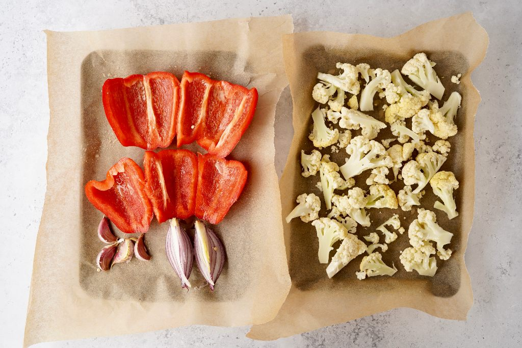 red pepper, red onions, garlic, and cauliflower on a baking tray
