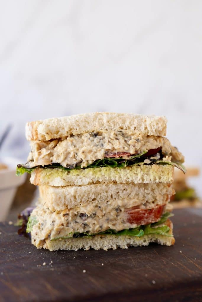 a chickpea tuna sandwich cut in half to show the fillings