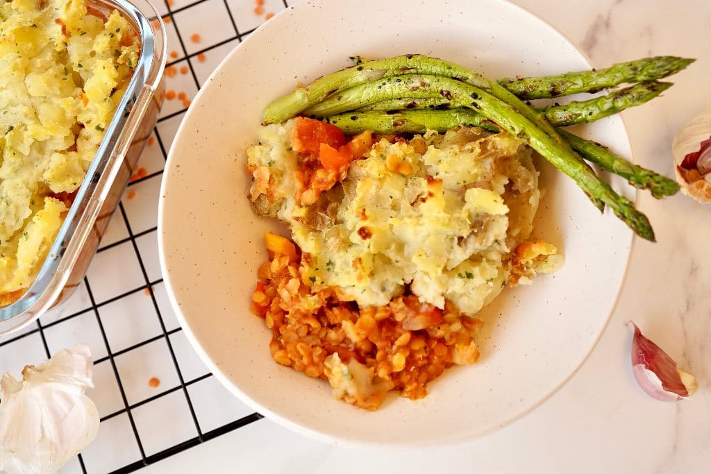 red lentil cottage pie with asparagus in a bowl next to garlic