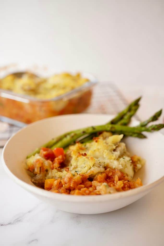 red lentil cottage pie with asparagus in a bowl